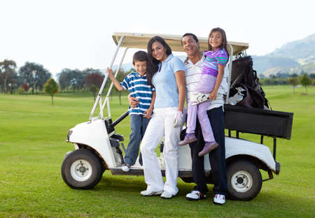 woman golf: Beautiful family portrait with a golf cart at the course