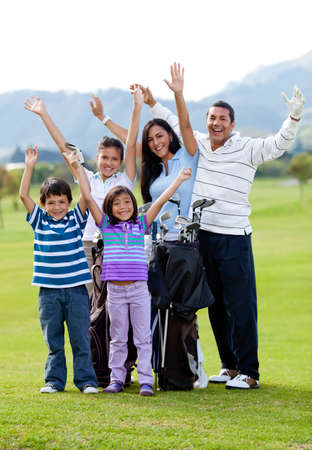 Happy family of golf player with arms up at the course Stock Photo - 12197973