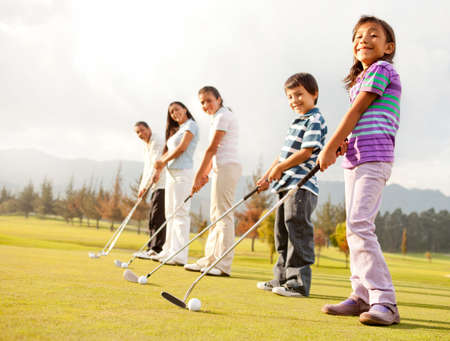 Golf players of all ages practicing to hit the ball at the course photo