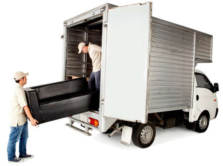 consignment: Delivery men loading a sofa in a truck - isolated over white