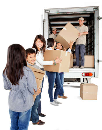 Family moving house and loading a truck with boxes - isolated over white photo