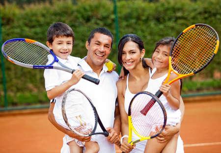 jugando tenis: Familia feliz jugando raquetas de tenis que sostienen en la corte Foto de archivo