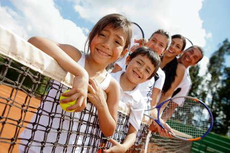 tenis: Familia de los jugadores de tenis en la corte junto a la red