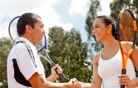 Couple handshaking at the tennis court after a match photo