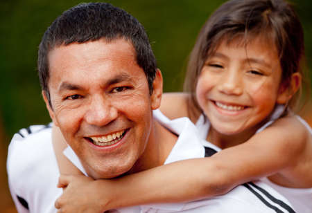 Portrait of a father and daughter at the tennis court smiling photo