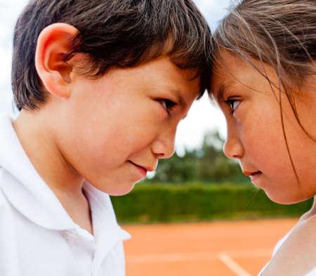 brat: Rywalizacja rodzeństwa - dwoje dzieci na korcie tenisowym patrząc konkurencyjny