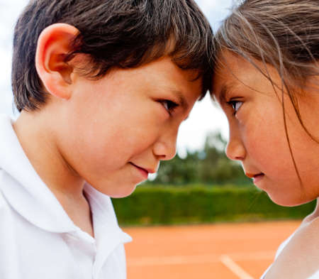 rival: Siblings rivalry - two kids at the tennis court looking competitive