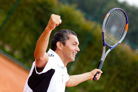 Man winning at tennis with arms up and holding a racket  photo