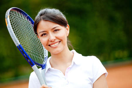 Female tennis player holding a racket and smiling photo