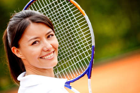 tennis clay: Beautiful woman holding a tennis racket at the court and smiling  Stock Photo