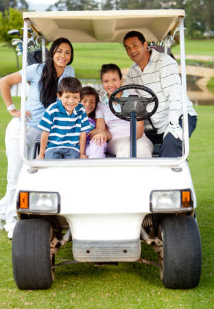 Family playing golf and riding a cart though the course  photo