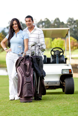 Couple playing golf posing with a cart and a bag smiling  photo