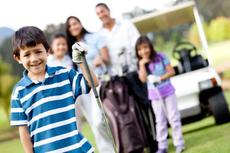 latin family: Boy playing golf with his family at the background