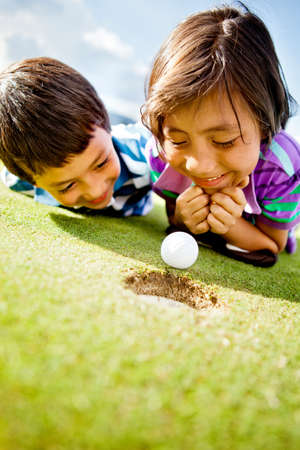 Young golf players staring at the ball to see if it goes in the hole photo
