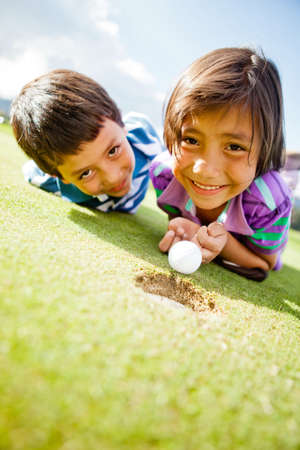 Kids enjoying playing golf lying on the field and smiling  photo