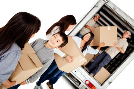 Family moving house and loading a lorry - isolated over a white background photo