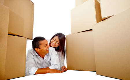 Loving couple moving house lying on the floor with boxes  Stock Photo - 12197889