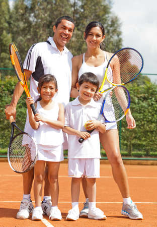 Happy family playing tennis holding rackets and smiling photo