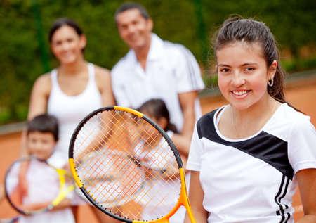 apoyo familiar: Joven jugador de tenis femenino con su familia en el fondo