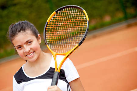Female teenager playing tennis, holding a racket and smiling  photo