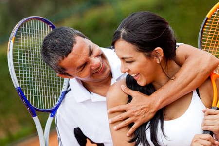 racket sport: Par de tenis coquetear en la corte y sonriente Foto de archivo