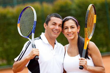 raqueta de tenis: Feliz pareja de tenis al aire libre la formaci�n de jugadores Foto de archivo