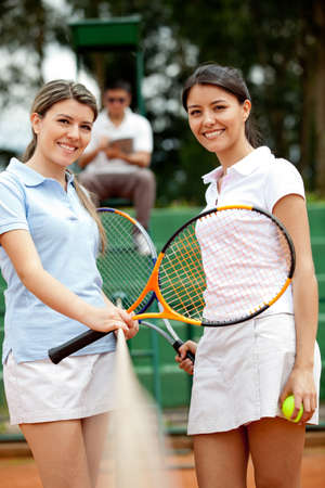 Lovely female tennis players at the court smiling  photo