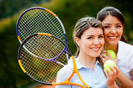 Friendly female tennis players holding rackets and smiling  photo