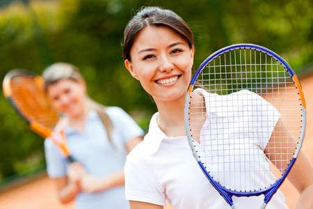 raqueta de tenis: Jugador de tenis femenino en el juego de dobles