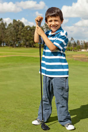 Young male golf player standing at the field with a golf-club photo