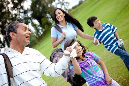 familia jugando: Familia jugando al golf y caminando hacia el siguiente hoyo