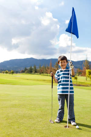 Boy with a golf flag in the hole at the course  photo