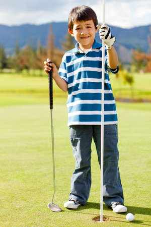 Boy at the course next to a hole playing golf  photo