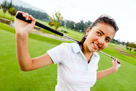 teen golf: Chica jugando al golf y la celebraci�n de un palo de golf en el campo Foto de archivo
