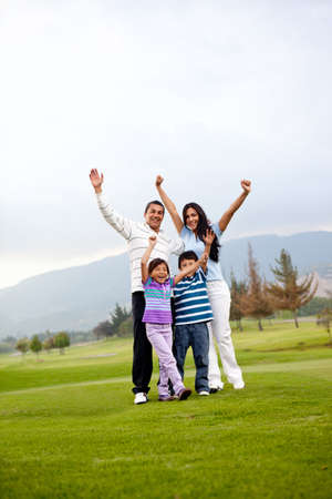 Happy family at the golf course with arms up photo