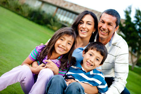 latinos: Happy family outdoors with a house at the background
