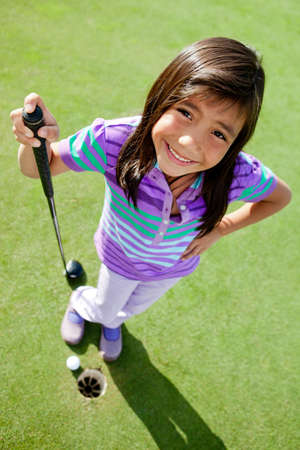 Young female golf player standing next to the hole photo