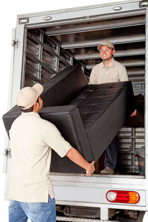 unload: Men working for a moving services company unloading a sofa from a truck
