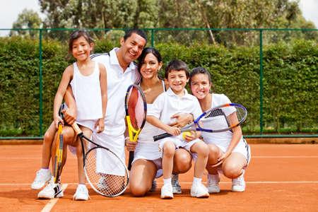 jugando tenis: Familia feliz jugando raquetas de tenis de cartera y la sonrisa
