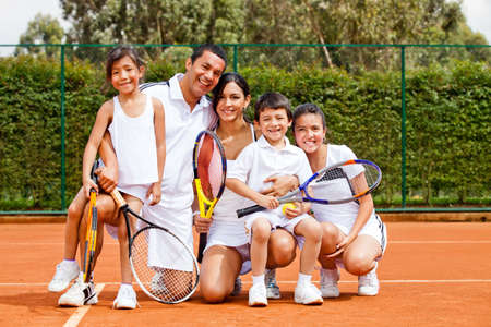 male tennis players: Happy family playing tennis holding rackets and smiling