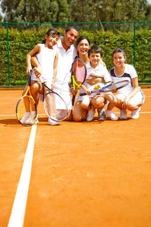 Happy family portrait at the tennis court  photo