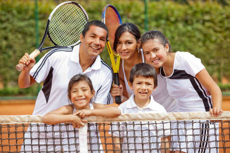 jugando tenis: Familia feliz jugando al tenis y la celebraci�n de raquetas Foto de archivo