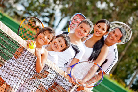 tennis clay: Tennis family standing in a row by the net  Stock Photo