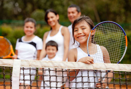 Girl tennis player with her family at the background photo