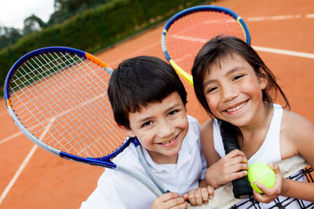 nios hispanos: Retrato de j�venes jugadores de tenis que sonr�e en la corte