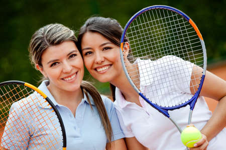 tennis clay: Beautiful female tennis players holding rackets and smiling  Stock Photo
