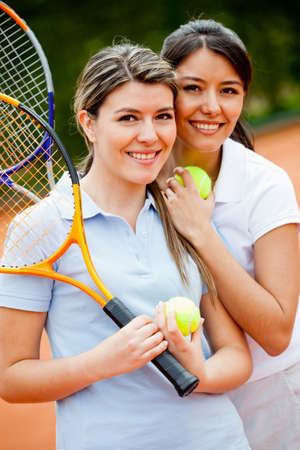 Beautiful female tennis players at the court smiling photo