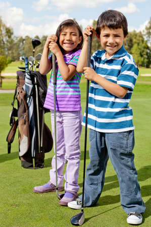 Casual kids at a golf field holding golf-clubs  photo