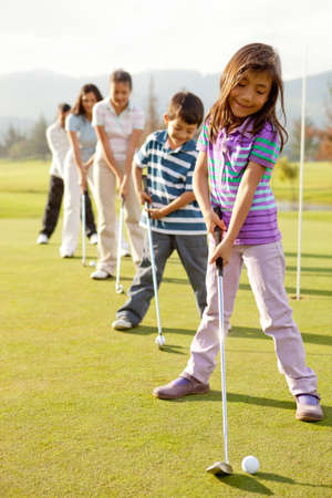 teen golf: Los jugadores de golf que practican para golpear la bola