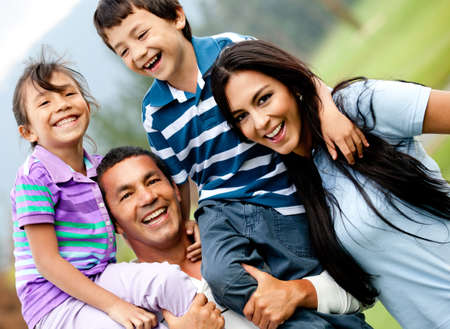 latin woman: Happy family having fun outdoors and smiling